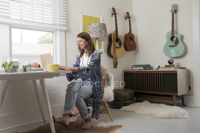 Mujer sentada en la mesa de comedor y usando computadora portátil - foto de stock