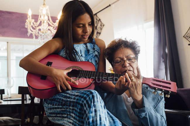 Grandmother teaching granddaughter to play guitar — Stock Photo