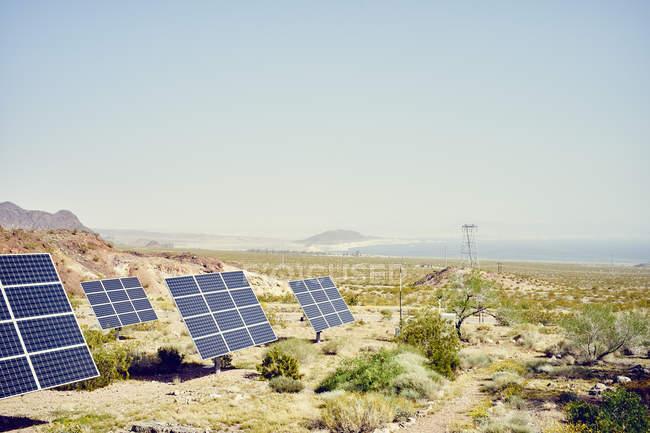 Ряд солнечных панелей в ландшафте с рекой Колорадо вдали — стоковое фото