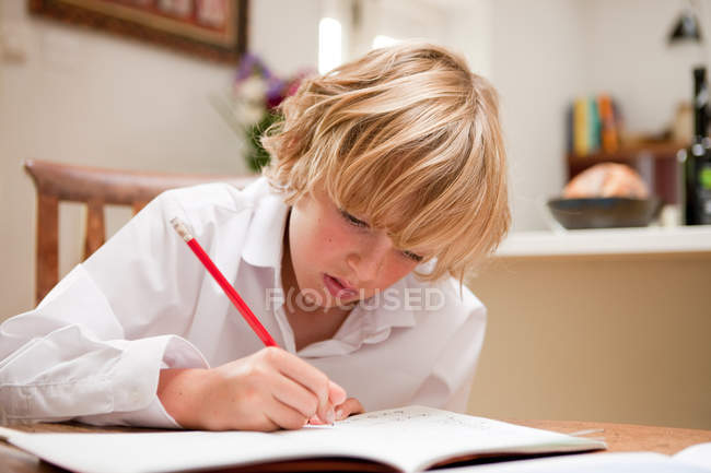 Young boy at home writing in school text book at the dining table — Stock Photo