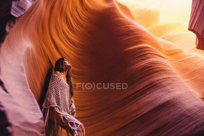 Женщина смотрит на солнечный свет в пещере, Каньон Антилопы, Пейдж, Аризона, США — стоковое фото