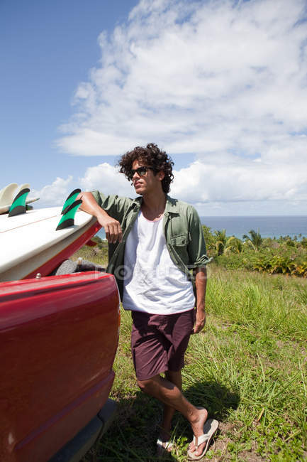 Young man leaning against surfboard in car, portrait — Stock Photo