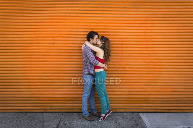Romantic couple kissing in front of orange shutter — Stock Photo