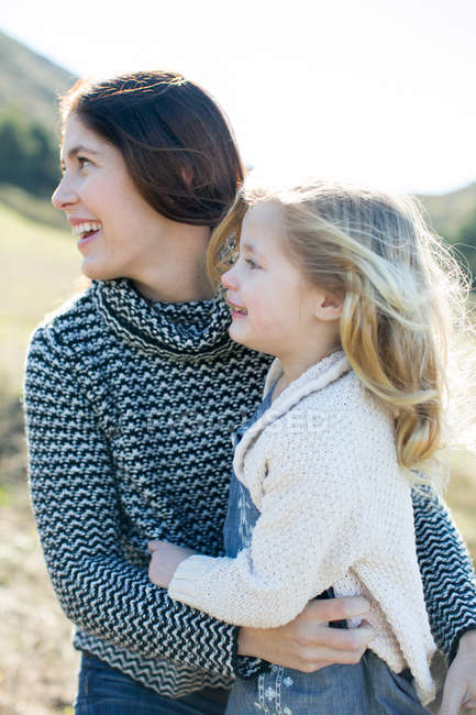 Mid adult woman and daughter looking over her shoulder in field — Stock Photo