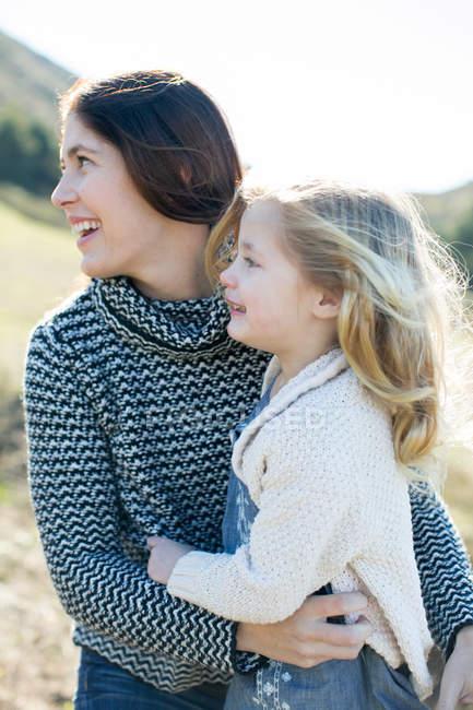 Mitte erwachsene Frau und Tochter schauen ihr im Feld über die Schulter — Stockfoto