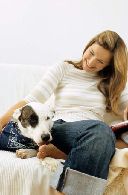 Cão e senhora proprietário no sofá — Fotografia de Stock