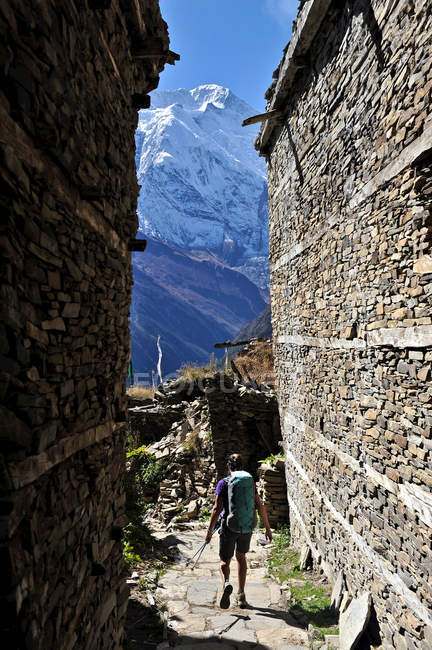 Donna trekking attraverso edifici medievali in pietra, Ghyaru, Nepal — Foto stock