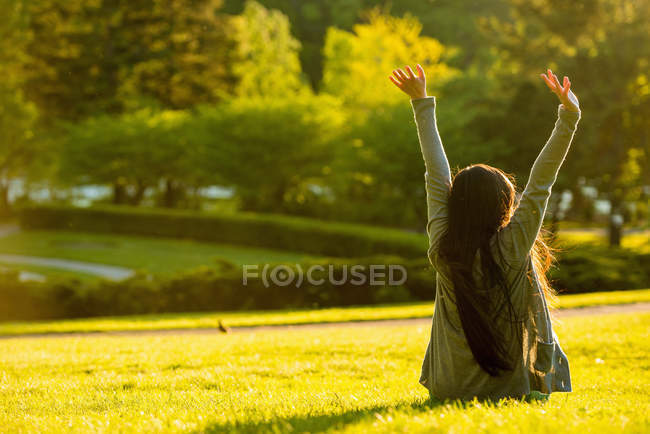 Rear view of young female sitting with arms raised in park — Stock Photo