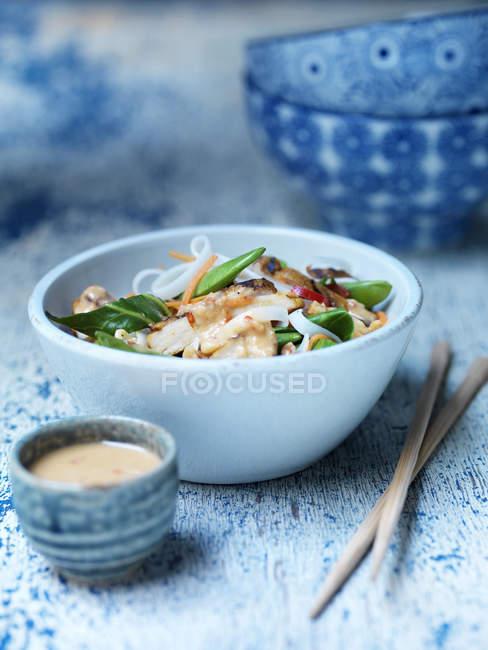 Schüssel mit würzigem Erdnusshuhn, Satay-Sauce, frischem Gemüse und Nudeln mit Stäbchen auf blauer Oberfläche — Stockfoto