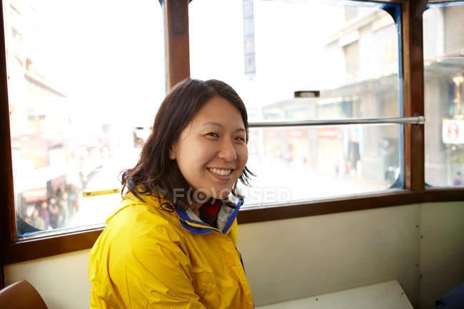 Porträt einer lächelnden Asiatin in der Straßenbahn — Stockfoto
