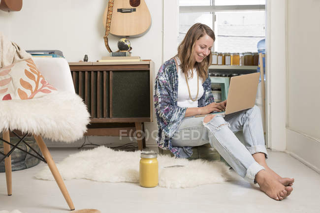 Mujer sentada en la sala de estar y usando computadora portátil - foto de stock