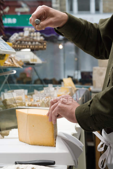 Cropped image of Cheesemonger cutting cheese — Stock Photo