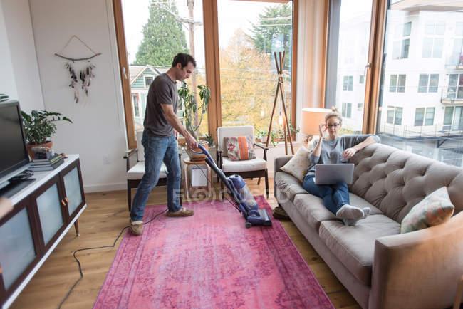 Man vacuuming carpet, girlfriend using laptop on sofa — Foto stock