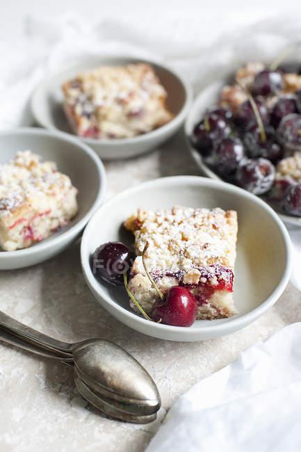 Porzioni di torta di ciliegie in ciotole sul tavolo — Foto stock