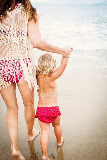 Back view of mother leading child on beach — Stock Photo
