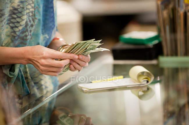 Commerçant, compter l'argent dans la boutique — Photo de stock