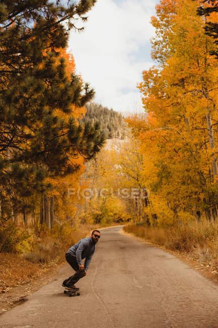 Homem jovem skate na estrada rural na floresta de outono, Mineral King, Sequoia National Park, Califórnia, EUA — Fotografia de Stock
