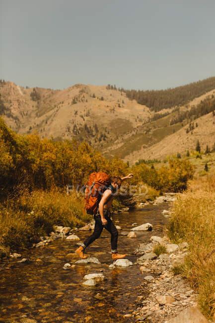 Mann mit Rucksack überquert Bach, Mineral King, Sequoia National Park, Kalifornien, USA — Stockfoto
