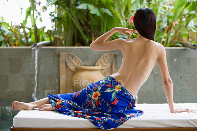 Задній вид жінка, сидячи на ліжку масаж — стокове фото