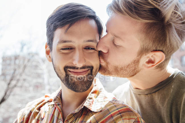 Portrait of male couple, mid adult man kissing his partner's cheek — Stock Photo