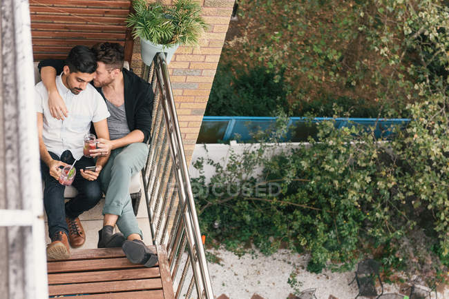 Young male couple hugging on apartment balcony, reading smartphone — Stock Photo