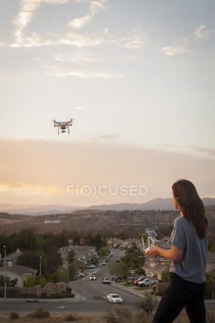 Operatore commerciale femminile che vola drone sopra lo sviluppo di abitazioni, Santa Clarita, California, USA — Foto stock