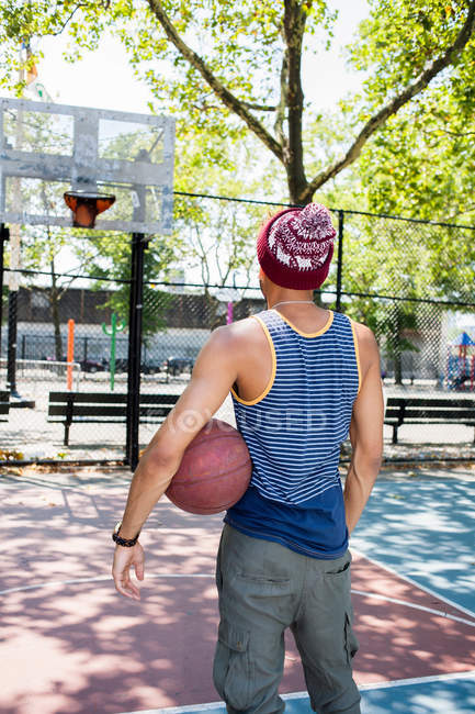 Young man looking towards basketball hoop on court — Stock Photo