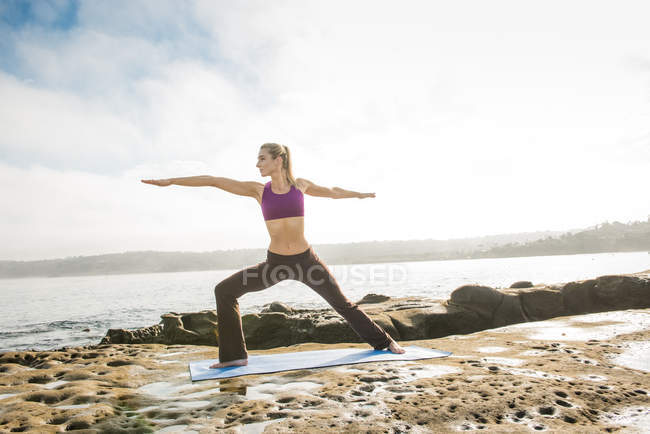 Woman doing yoga at coast — Stock Photo