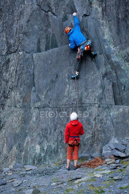 Vista trasera de alpinistas escalar la cara escarpada de la roca - foto de stock