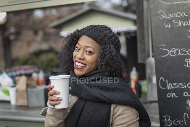 Portrait of woman having coffee  enjoying city during winter holidays by outdoor cafe — Stock Photo