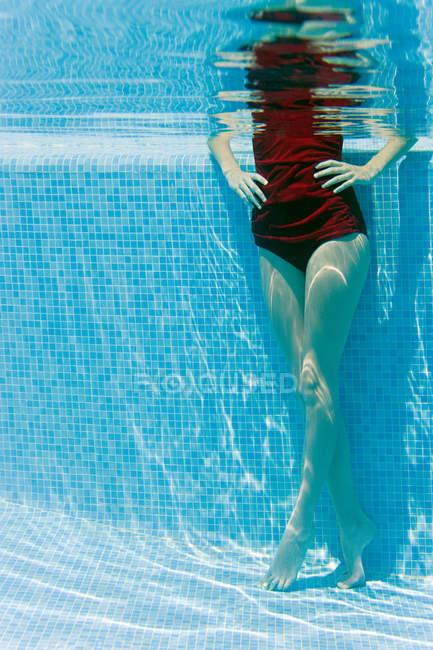 Femme debout les mains sur les hanches dans la piscine, vue sous l'eau — Photo de stock