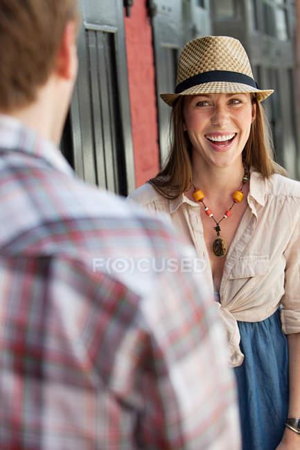 Jeune femme souriant à l'homme à l'extérieur — Photo de stock
