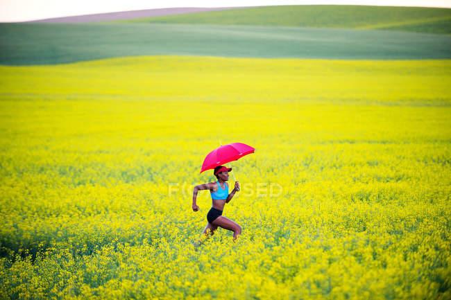 Молода жінка працює в масло насіння гвалтують сферу з червоним парасольку — стокове фото