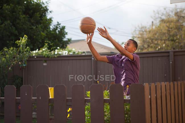 Мальчик бросает баскетбол возле забора — стоковое фото