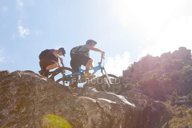 Jovem casal em bicicletas de montanha em rochas — Fotografia de Stock