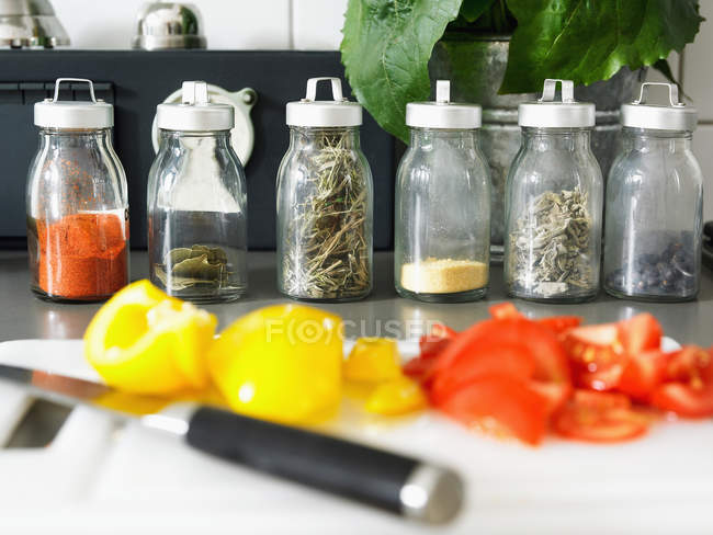 Cooking ingredients on cutting board and herbs in jars — Stock Photo