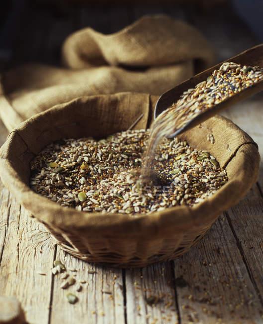 Mix di semi di zucca, girasole, papavero e lino versamento nella ciotola di vimini — Foto stock