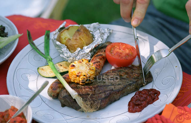 Cropped image of man cutting steak on plate — Stock Photo