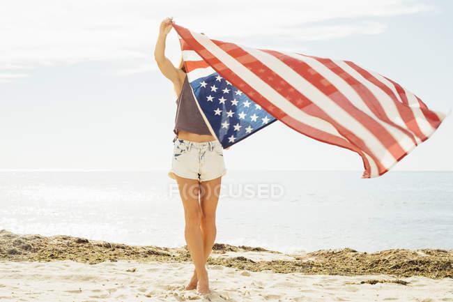 Женщина с американским флагом на пляже — стоковое фото