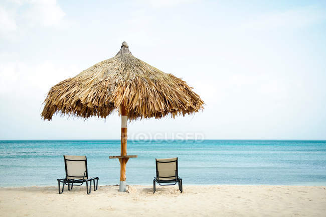 Парасолька та шезлонги на пляжі — стокове фото