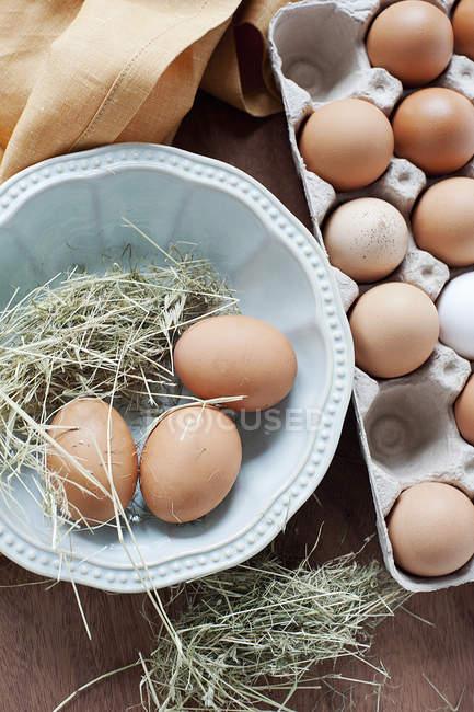 Ovos frescos e palha na tigela, vista superior — Fotografia de Stock
