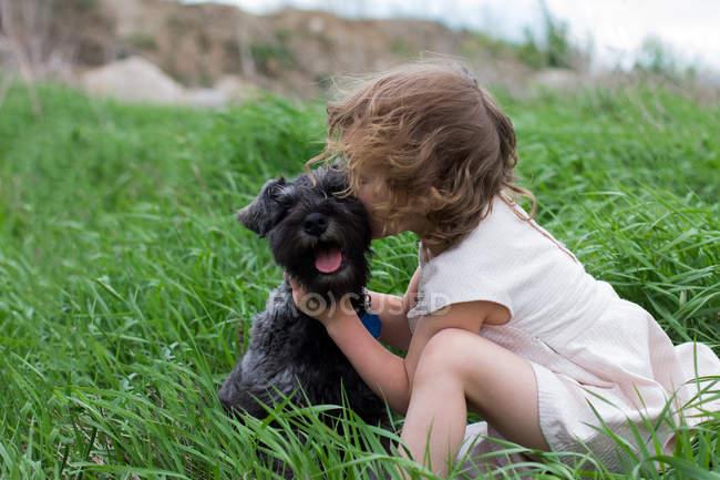 Little girl kissing pet dog on grass field — Stock Photo