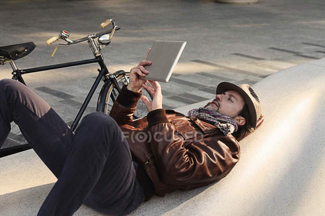 Mid adult man lying on back using digital tablet — Stock Photo