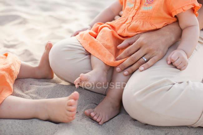 Mère assise avec les filles sur la plage, de faible section — Photo de stock