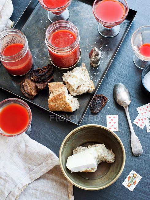 Stillleben von Tomatensaftgläsern, Brot und Käse — Stockfoto