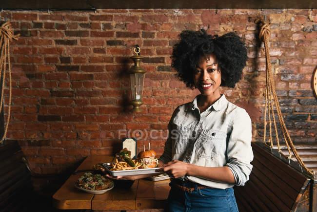 Официантка с тарелками бургера и картошкой фри в кафе — стоковое фото