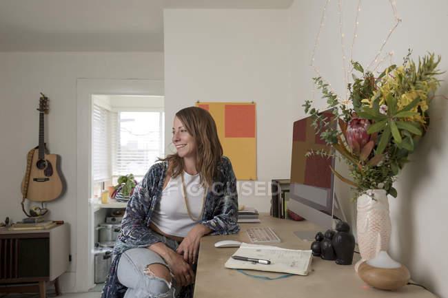 Mujer sentada en el escritorio y mirando hacia otro lado - foto de stock