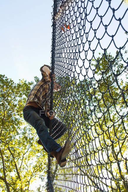 Homem adulto médio escalando cerca de elo de corrente — Fotografia de Stock