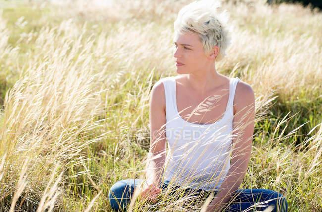 Giovane donna in campo erboso — Foto stock