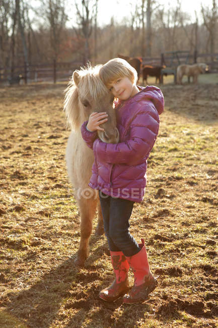 Portrait of young girl outdoors, hugging pony — Stock Photo